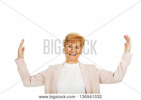 Happy elderly business woman try to catch something