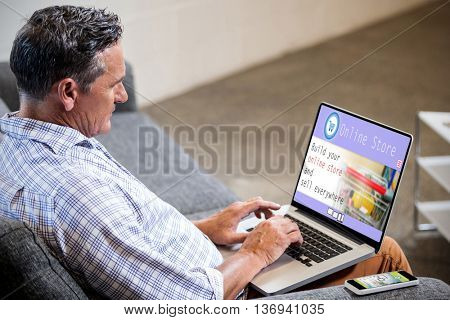 Screen of an online store against profile view of a businessman working on computer