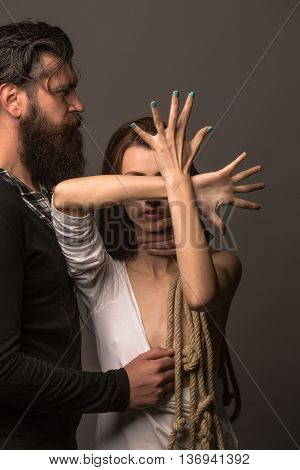 young couple of pretty naked woman with bare chest has rope on hands and handsome beard man with long beard touching female breast on grey background