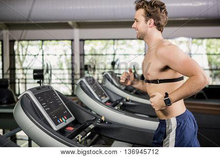 Man running on thread mill at gym