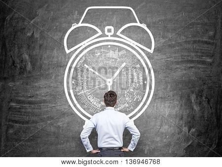 Time management concept with thoughtful businessman looking at chalkboard wall with alarm clock sketch