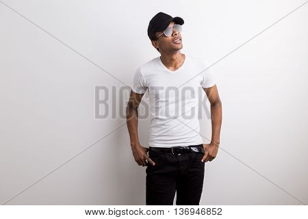 Stylish smiling black guy in shades and cap looking away from the camera on light background with copy space