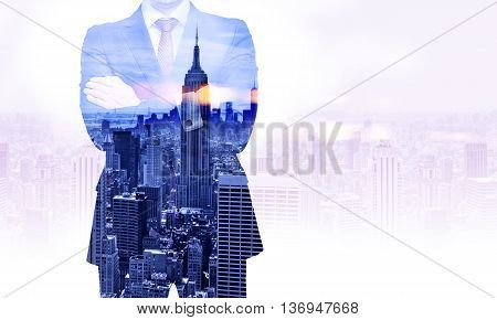 Front view of businessman with crossed arms on New York city background. Double exposure