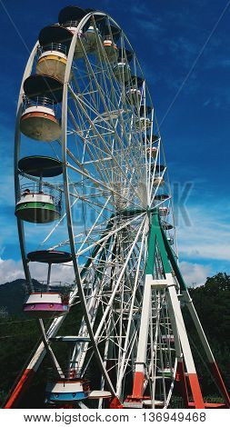 Here's a Ferris wheel in forest. Colorfull wheel. And very Blue sky