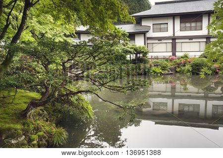 Japanese zen garden and pond with traditional building on distant shore