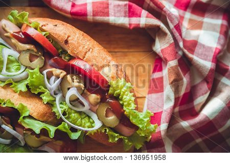 Hotdogs with fresh salad and tomatoes on wooden Board