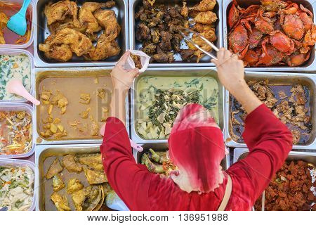 Variety of delicious Malaysian home cooked dishes sold at street market stall in Kota Kinabalu Sabah from top angle view with seller in motion taking food.
