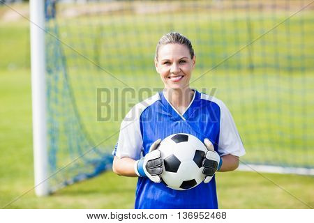 Portrait of female goalkeeper standing with a ball