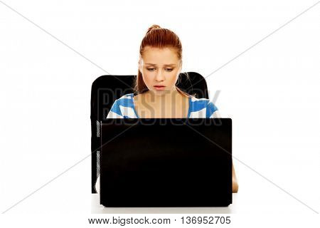 Teenage angry woman with laptop sitting behind the desk