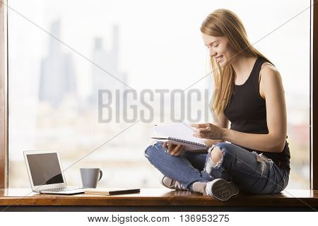 Smiling young woman with notepad in hand sitting on windowsill with blank laptop screen. Blurry city view in the background. Mock up