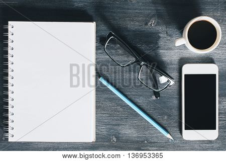 Top view of wooden office desktop with blank mobile phone spiral notepad coffee cup glasses and pencil. Closeup Mock up