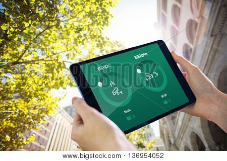 Hands holding tablet against low angle view of buildings and tress