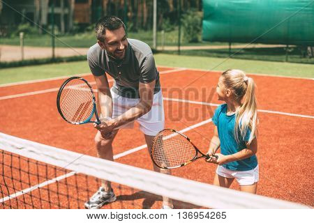 Practicing tennis. Cheerful father in sports clothing teaching his daughter to play tennis while both standing on tennis court