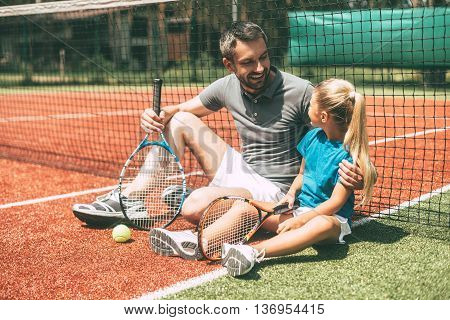 Relaxing after good game. Cheerful father and daughter leaning at the tennis net and looking at each other with smiles while both sitting on tennis court