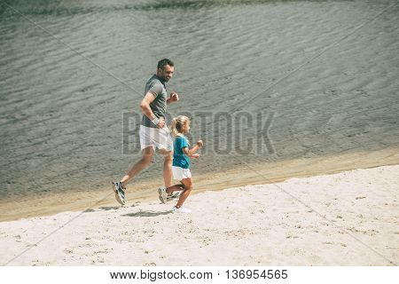 Enjoying jogging on fresh air. Top view of cheerful father and daughter in sports clothes jogging at the riverbank together
