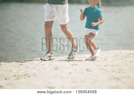Jogging with father. Close-up of little girl and her father running along the riverbank together