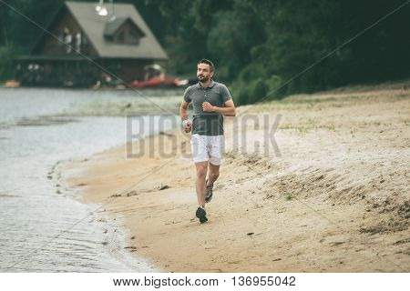 Keep running. Full length of confident man in sports clothing running along the riverbank