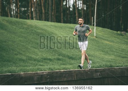 Enjoying morning jog. Full length of confident man in sports clothing wearing headphones and running in park