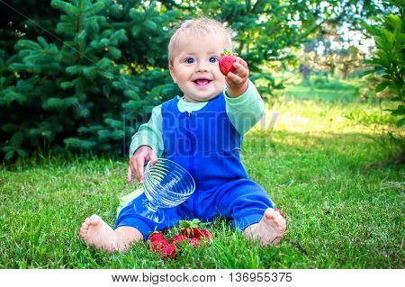 Cute smiling little baby sitting on a fresh green grass in a park and giving fresh sweet strawberry to the viewer