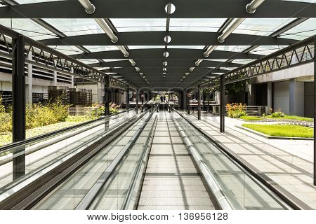 Modern business architeture: Car parking area with moving walkway and unidentified people in the distance