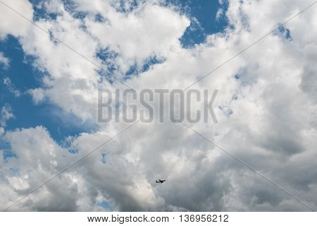 Small airplane in the bottom center flying high in dramatic clouds as seen from the ground with large space for your copy text