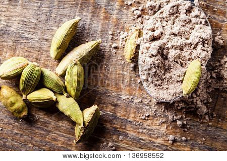 Tablespoon of ground cardamom and pods on wooden table. Top view.