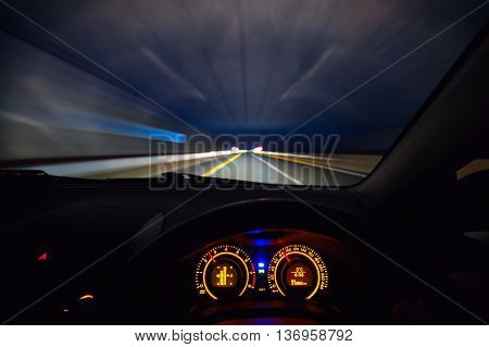 Driver view at speeding car dashboard and motorway at night