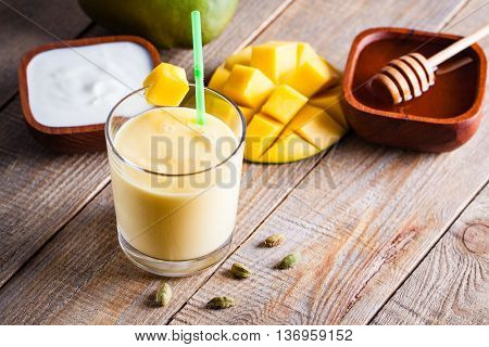 Glass of mango lassi Indian drink flavored with cardamom. Milkshake on wooden background.