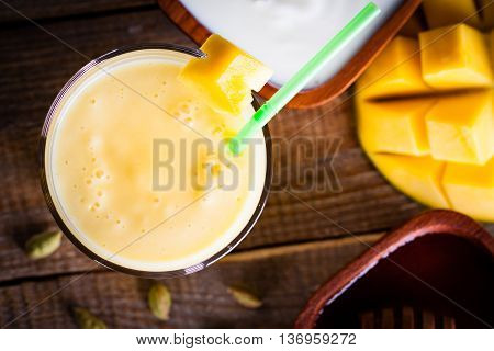 Overhead glass of milkshake made of mango and yoghurt with sweet honey.
