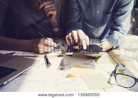 Photo Woman Hand Touching Digital Tablet Screen.Analytics Department Researching Process.Young Business Crew Working New Startup modern Studio.Analyze markets stocks.Blurred, film effect.Horizontal