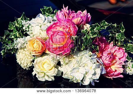 Decorative flowers bouquet on black wedding car taken closeup.