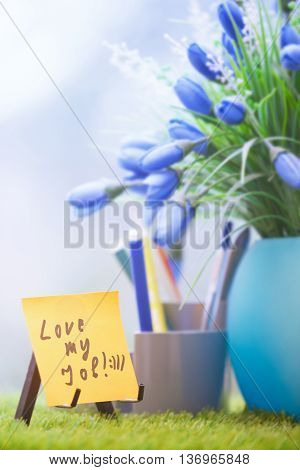 Adhesive note with Love my job text at green office
