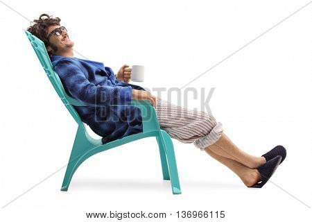 Relaxed man sitting on a blue plastic chair and holding a cup of coffee isolated on white background