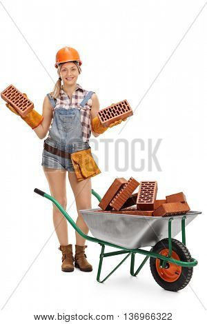 Full length portrait of a female construction worker holding bricks and posing by a wheelbarrow isolated on white background