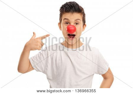 Excited kid pointing to a red clown nose on his face isolated on white background