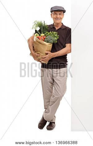 Full length portrait of a senior man holding a grocery bag and leaning against a wall isolated on white background