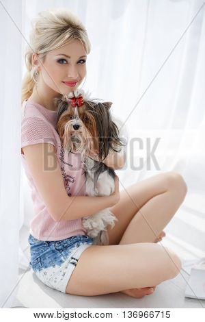 Beautiful woman,blonde hair,nice smile and light makeup,my ears gold earrings,dressed in a pink blouse,holding a beloved friend-the dog breed Yorkshire Terrier with a red bow on her head, sitting near a large bright window