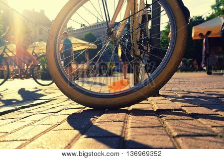 The wheel of a bicycle parked on the square on the background of tourists. Backlight