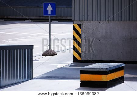 Traffic sign on an empty parking with a striped orange paint with a warning about the dangers of