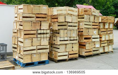 Row of four pallets stacked high with wooden crates.