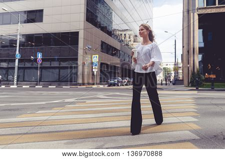 Beautiful woman crossing on crosswalk and holding cup of coffe. Split toned photo