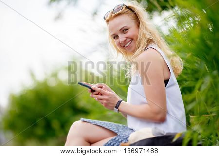 Beautiful smiling young woman with phone sitting in a Park surrounded by greenery. Image with tilt-shift effect