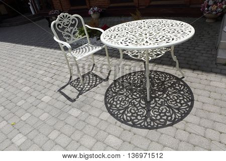 metal chair and metal table on the pavement