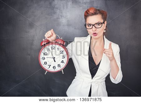Beautiful Strict Teacher With Clock On Blackboard Background