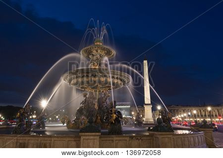 Obelisk of Luxor and fountain with water motion at the Place de la Concorde in Paris at night