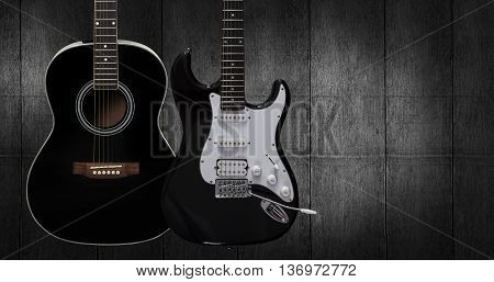 Acoustic and electric guitar on dark black wooden background.