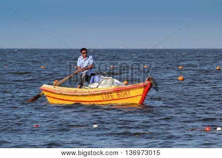 Beidaihe China. August 9 2012. A man in a wooden lifeboat.