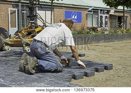 YSBRECHTUM, THE NETHERLANDS - JULY 4, 2016: Photo of a male bricklayer using a rubber hammer to beat black bricks on right place.
