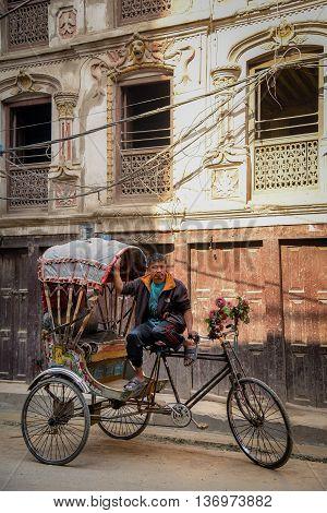 KATMANDU NEPAL - APRIL 7 2016 : Traditional nepalese rickshaw parked on the Thamel street with nepali driver.
