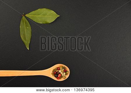 Two Bay Leaves And Pepper On Black Chalkboard